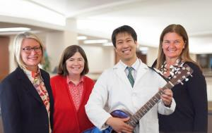 Matthew Sakumoto, MD plays the guitar as other attendees surrounds him