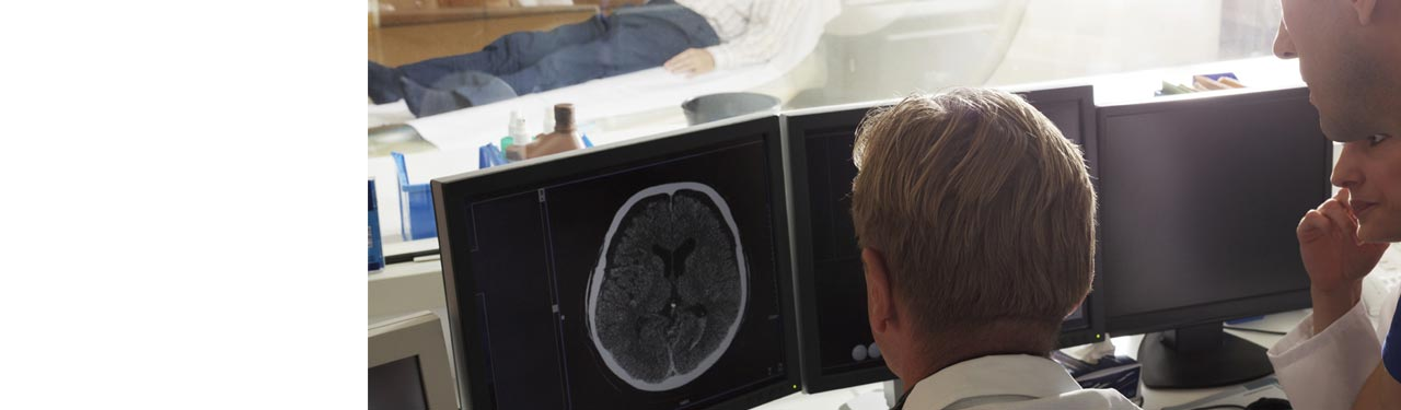 Doctors looking at a brain scan on a monitor