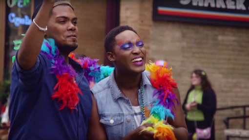Two men wearing a rainbow boa celebrating Chicago Pride