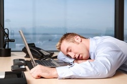 Male sleeping at his office desk