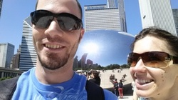 Adam Crothers stands next to the Cloud Gate with a friend