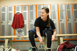 Young female athlete sitting on locker room bench