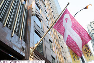 Pink flag hangs from building for Cancer Care month