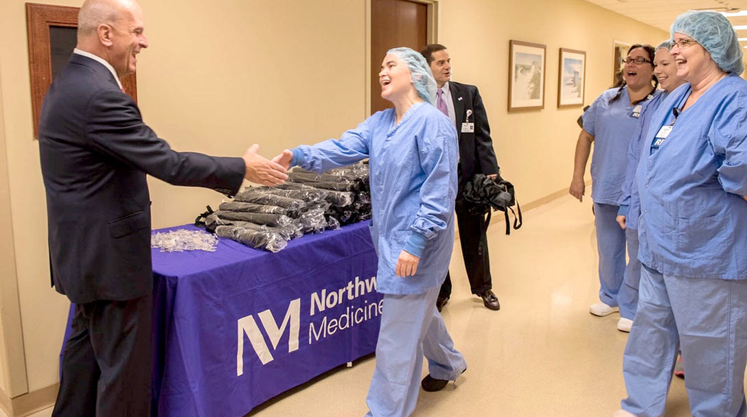 Northwestern Medicine leader shaking hands with a female medical staff member as others look on