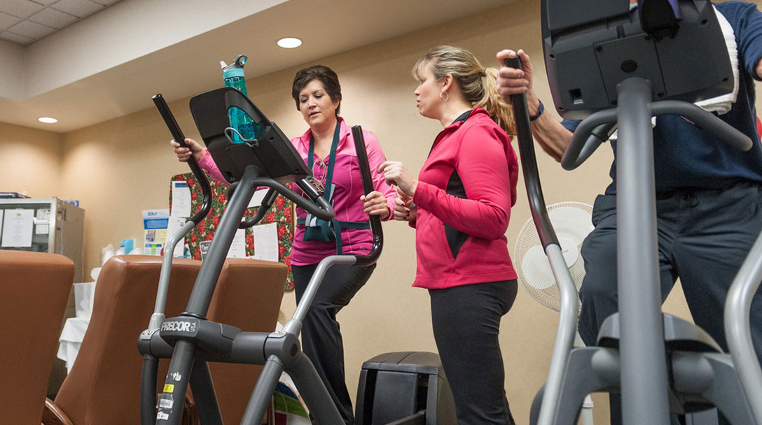 Sherry Kim on fitness machine being monitored by medical professional