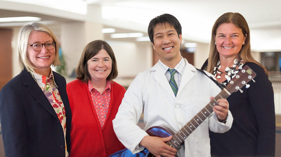 Women with doctor holding a guitar at Tune Up event to raise awareness
