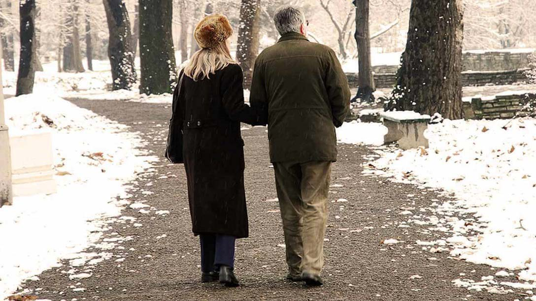Senior Citizen Couple Walking on Snowy Path