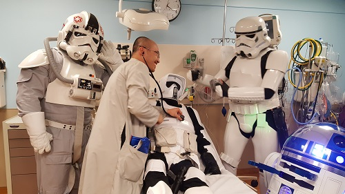 Dr. Brian Hang, a pediatric emergency medicine physician at Northwestern Medicine Central DuPage Hospital, pretends to save Chris Kowalski, an Oswego 'Star Wars' fan dressed as a Biker Scout.