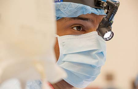 A close-up of a physician in scrubs about to perform surgery.