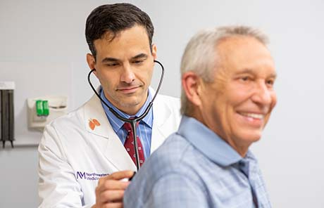 A Northwestern Medicine pulmonary physician listening to a male patient