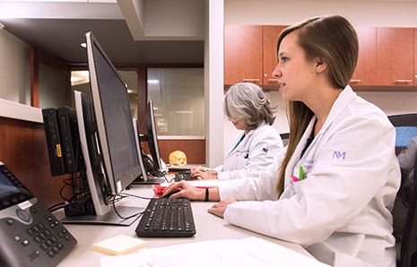 Two physicians with the Head and Neck Cancer Program working at their computers.