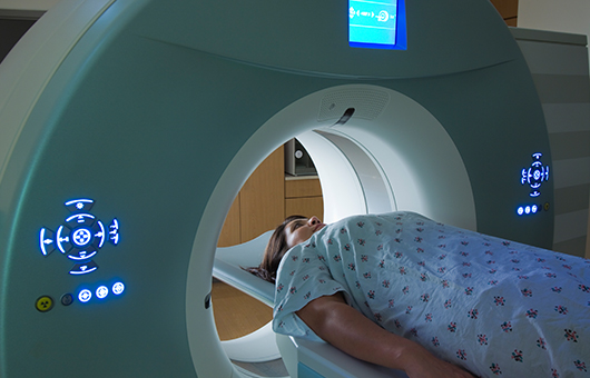 female patient entering pet/ct scanning machine positron emission tomography
