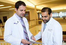 Two Movement Disorders Centers of Excellence physicians reviewing a patient chart.
