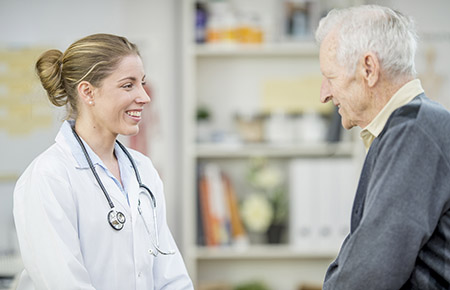 A female physician talking with an elderly male neurobehavior and memory clinic patient.