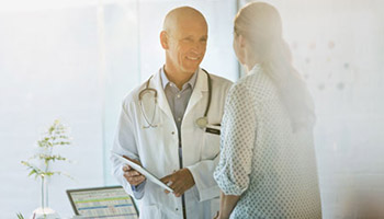 A movement disorders physician talking with a patient.