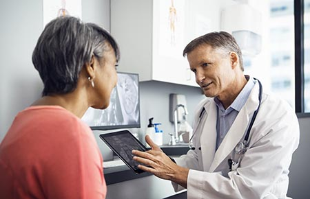 A physician consulting with a female patient about her joint replacement.
