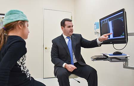 Northwestern Medicine Joint Replacement surgeon Dr. Benjamin Davis showing an X-ray to a patient.