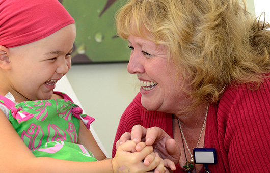 Cadence volunteer laughing with childhood cancer patient