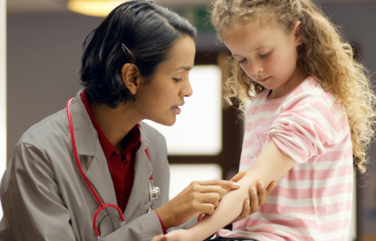 Doctor pointing to arm on young patient
