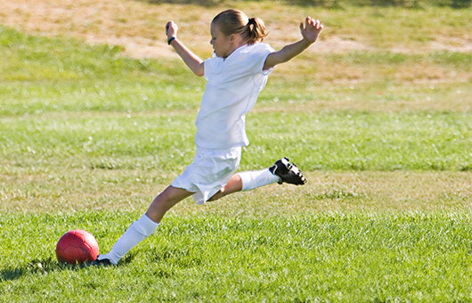 Girl on soccer field kicking ball