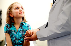 Young girl looking up at doctor