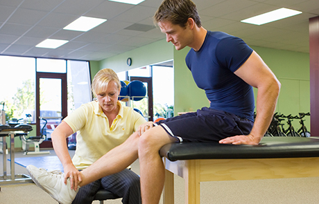 Physical therapist working on patient knee