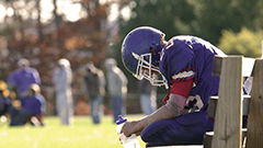 Football player resting on bench