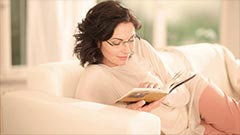 Woman reading a book laying on the couch