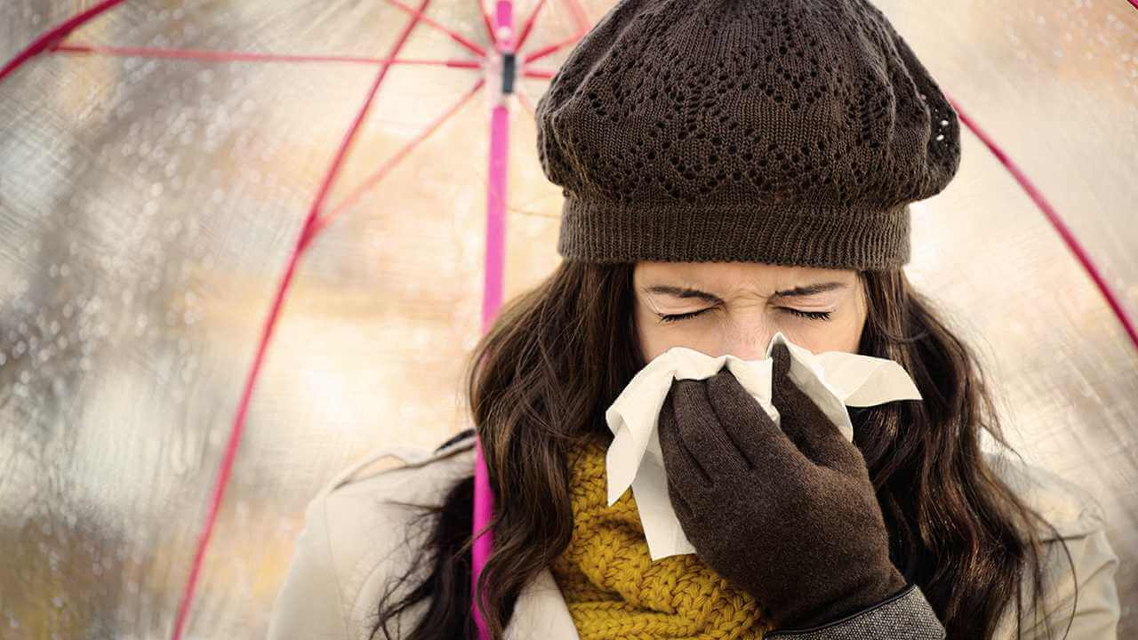 woman sneezing with flu
