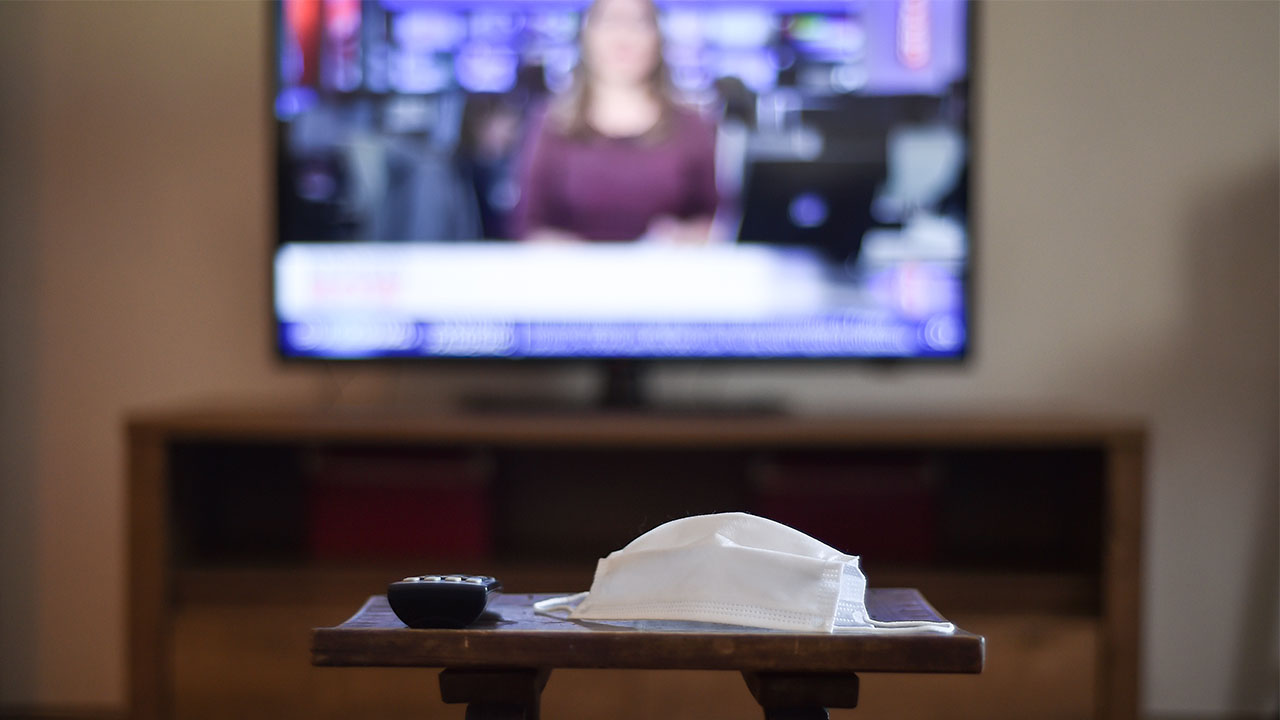 television remote control and a medical mask, with news channel open in background