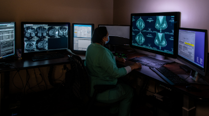 A northwestern medicine physician examining breast imaging on several computer screens.