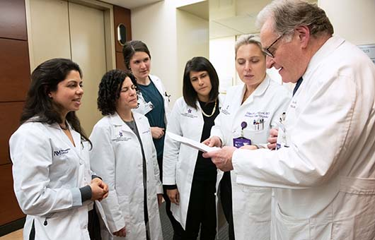 A team of Northwestern Medicine cancer physicians reviewing paperwork.