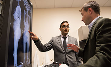 Northwestern Medicine Spine Surgeons Dr. Tyler Koski and Alpesh Patel reviewing a patient's spine scans.