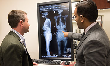 Northwestern Medicine doctors Tyler Koski and Alpesh Patel reviewing a patient's spinal injury.