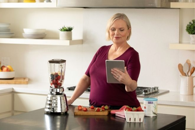 Woman looking at IPad and making a smoothie