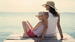 Mother and daughter sitting on a dock in the sun