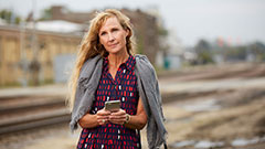 woman holding phone by train tracks