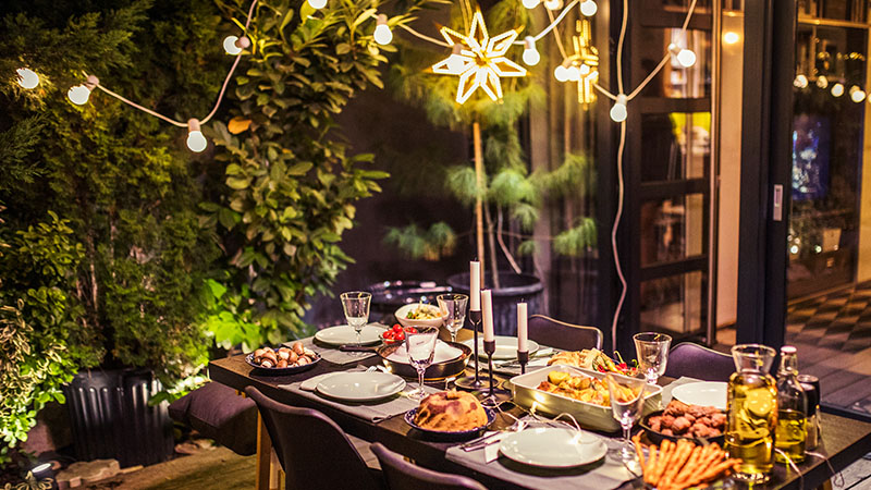 table set for dinner party in backyard with string lights