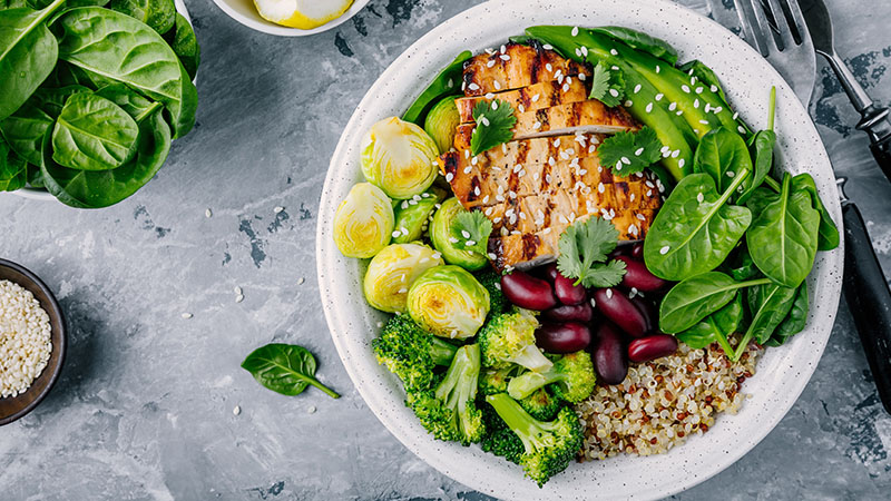 bowl of grilled chicken breast, bright green veggies and quinoa