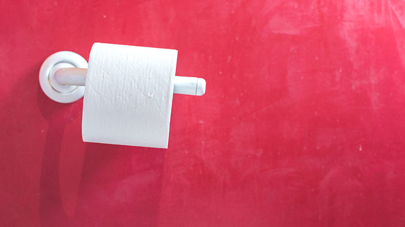 roll of toilet paper against red wall