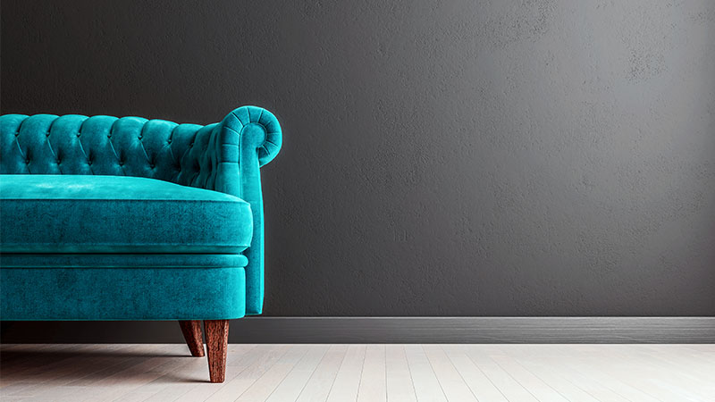 Living room dark grey wall with turquoise velvet sofa, with free space to the right